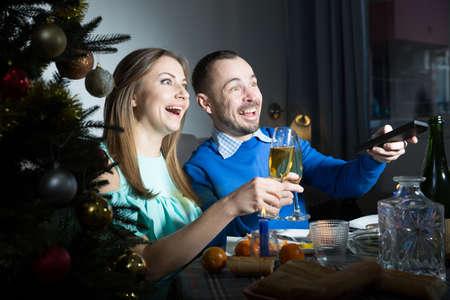 Man and woman watching tv at Christmas night