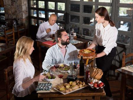 Waitress bringing meals to visitors