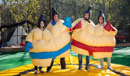 Friends posing in inflatable sumo suits Archivio Fotografico
