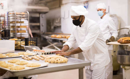 Baker at work in protective mask - making sweet buns with dough