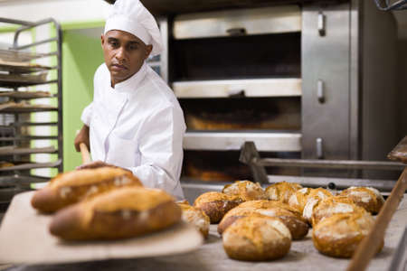 Male baker pulls hot bread out of the oven at bakery