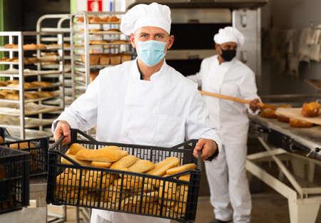portrait of european male baker with mask in bakery Stock fotó