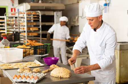 man in chefs uniform kneading dough in bakery