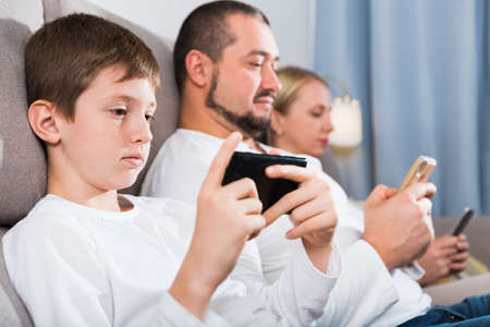 Modern family with smartphones at home Foto de archivo