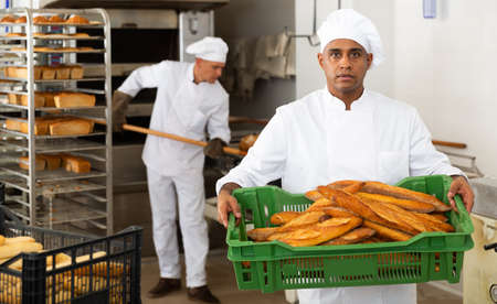 Male baker holding crate with baked bread
