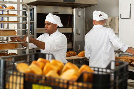 Confident baker carrying rack trolley with bread Banco de Imagens
