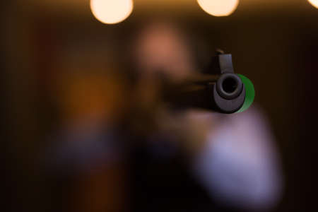 Muzzle of single barrelled shotgun on blurred background of aiming man Banque d'images