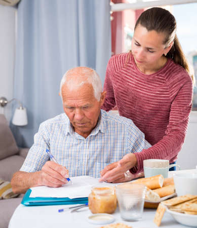 Portrait of mature father and daughter with documents