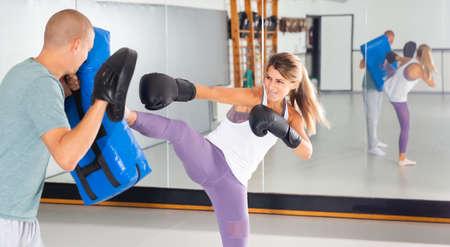 Concentrated woman kicking boxing shield Standard-Bild