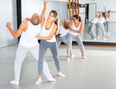 Girl practicing effective self defence techniques in training room