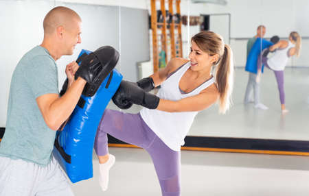 Concentrated active woman kicking boxing shield