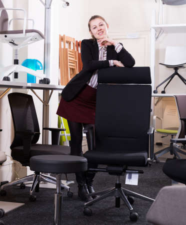 Saleswoman standing in chair store