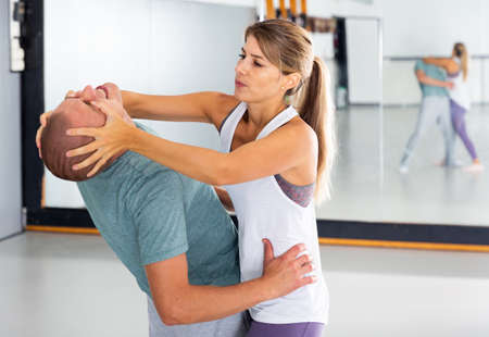 Sporty woman with a trainer conducts painful reception on the eyes in gym