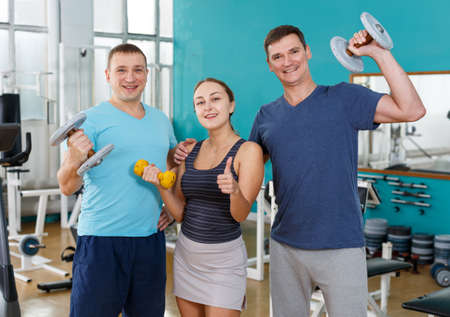 Three people holding sport equipment in gym