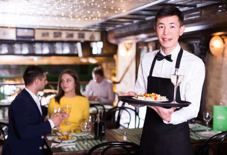 Portrait of male waiter who is holding tray with order Imagens