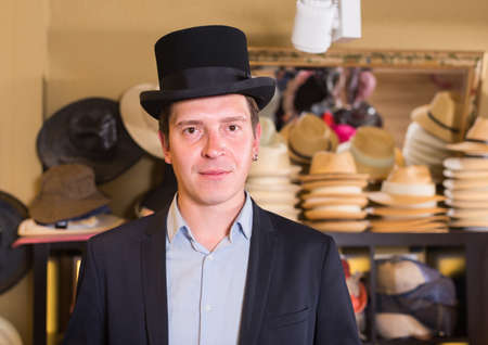 cheerful adult male shopping in botique and try on cylinder hat