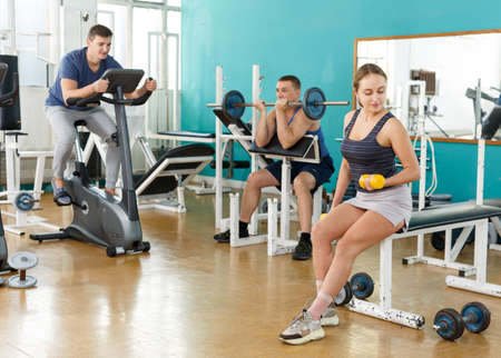 Sporty girl with dumbbells foreground