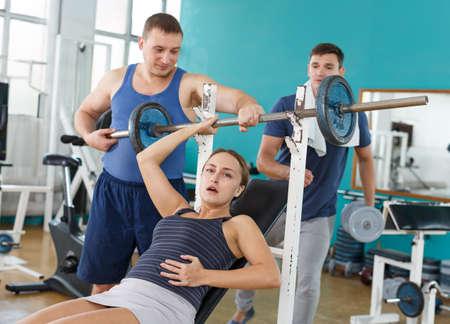 Men helping injured woman in gym