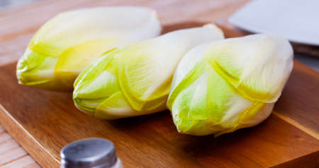 Raw organic endives on wooden table