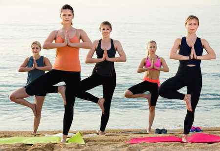 Group of young females performing yoga