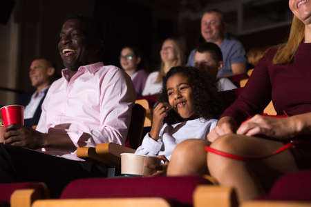 international parents with children laughting at movie in cinema