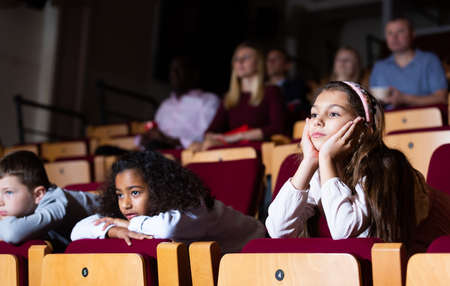 kids sitting at perfomance in theatrical auditorium