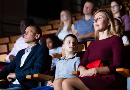 Family of theatergoers with preteen son watching performance in theater