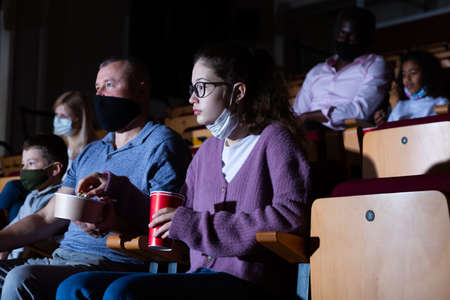 Father with his teenage daughter eating popcorn and watching a movie in cinema