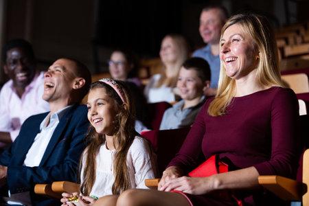 caucasian family sitting at funny premiere in cinema Foto de archivo