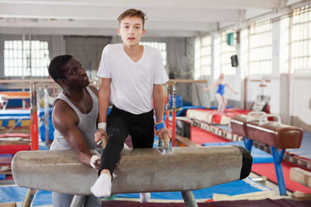 trainer helping teenage athlete with exercise technique