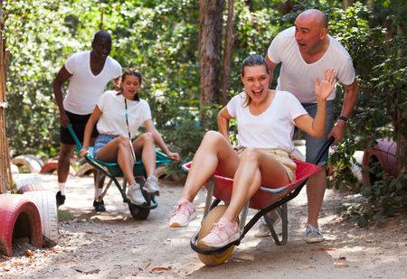 Men drive their girls in garden wheelbarrows. Funny amusement park amusement park