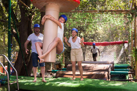 Friends help each other overcome water obstacles in theme park
