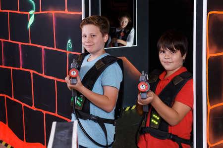 Two joyful teen boys standing with laser guns