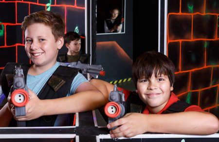 Two happy teen boys standing with laser guns Stock Photo
