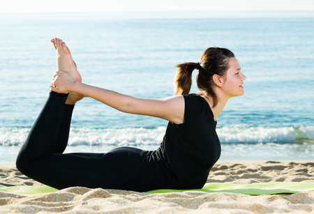 Portrait of sportswoman which is practicing asana in black T-shirt