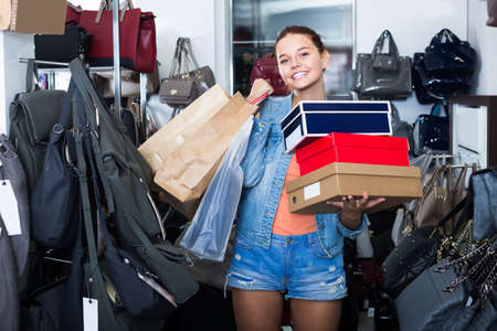 joyous teenager girl holding boxes in shoes boutique