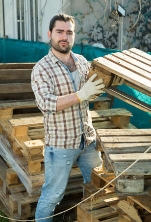 Man laying wooden pallets