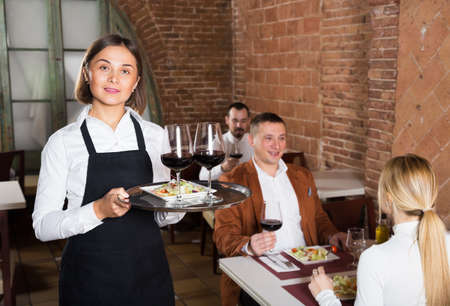 Happy female waiter showing country restaurant