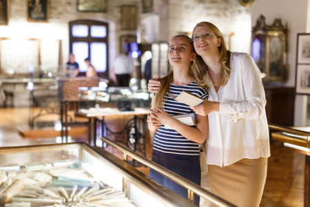 Woman visitor with daughter looking to art objects under glass with guide book