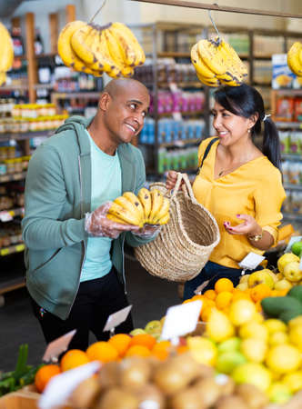 Couple choosing bananas in fruit and vegetable section of supermarket