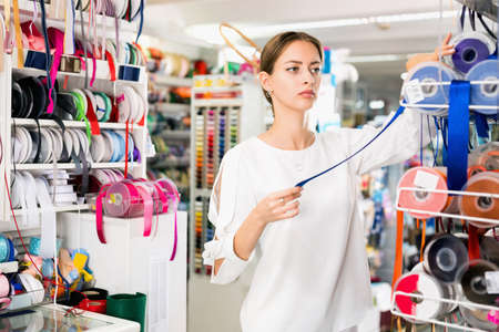 Interested young woman choosing colorful ribbons and braid for dressmaking in sewing supplies shop
