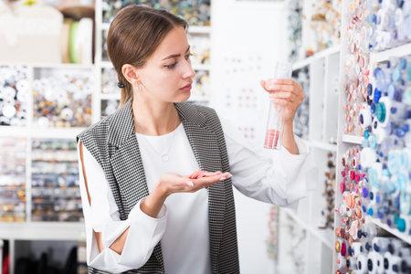 Woman choosing buttons in needlecraft store