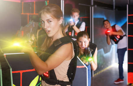 men and women playing emotionally laser tag game in arena