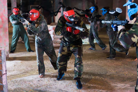 Young people playing paintball
