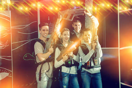 Happy young people with laser pistols posing together on dark la
