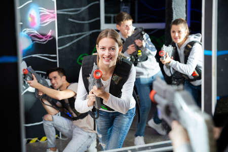 Portrait of excited woman holding laser gun in arena, playing laser tag game with friends