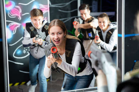 Smiling girl with laser guns took aim and having fun with friends