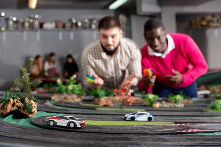 Portrait of two african and caucasian men playing with slot car racing