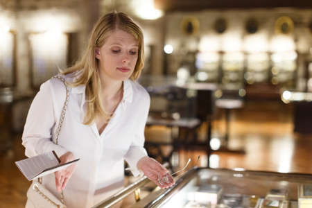 Woman visitor looking to art objects under glass with guide book in museum