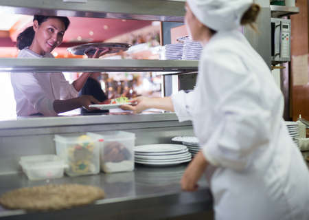 Smiling waitress taking cooked meals in restaurant kitchen Banque d'images